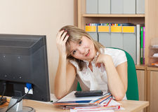 Weariness woman  in  office. Weariness woman  sitting with documants  on workplace in  office Royalty Free Stock Images