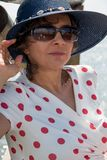 Wearing夫人在海滩附近的一个蓝色帽子 免版税图库摄影