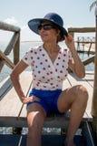 Wearing夫人在海滩附近的一个蓝色帽子 免版税库存图片