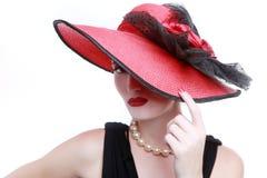 Wearing夫人在白色背景的一个红色帽子 免版税库存图片