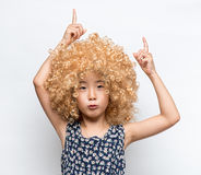 Wearing a blonde wig and funny facial expression Asian girl Stock Photography