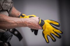 Wearing Safety Gloves. Wearing Construction Safety Gloves Closeup Photo. Caucasian Contractor Preparing For a Job stock photos