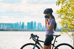 Free Wearing Covid-19 Mask While Riding Bike. Sport Cyclist Woman Biking Putting On Face Mask For Covid-19 Prevention During Royalty Free Stock Photos - 191473188
