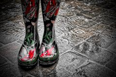 Wearing Decorative Red Rain Boots in the rain on pavers. The female model is wearing rubber red decorative rain boots in standing water.  The rain is light right Royalty Free Stock Photos
