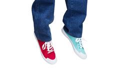 Wearing different sneakers. Wearing jeans and different sneakers on legs Stock Photography