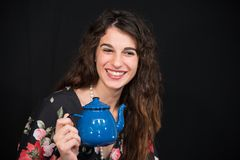 Beautiful teenage girl smiling, with long wavy brown hair holding a blue teapot in her hand. stock photo