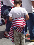 Wearing the Flag. A young boy wears a flag as his marches with his family at A Day without an Immigrant on May 1st in Los Angeles, California Royalty Free Stock Photography