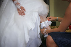 Wearing garter on leg of bride. Hand fastening garter on leg of bride in traditional white wedding dress Royalty Free Stock Images
