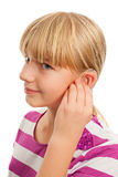 Wearing a hearing aid. Teen girl wearing a hearing aid. Studio shot-isolated on white background stock images