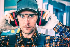 Wearing Hearing Protectors. Factory Worker Wearing Hearing Protectors and Protective Goggles royalty free stock photo