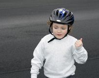 Wearing Helmet. Young boy wearing bicycle helmet while standing on blacktop Royalty Free Stock Photography