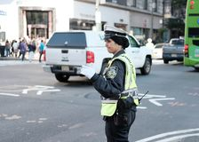 NYPD Traffic Policewoman seen directing traffic in Manhattan, NYC. Wearing hi-vis gear, the policewoman is on a busy intersection in downtown New York city Stock Photo