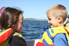 Wearing a life jacket. Boy and girl in a boat with a life jacket going fishing Royalty Free Stock Image