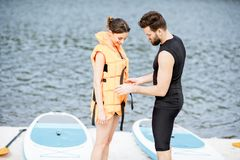 Wearing life vest on the beach. Male instructor helping to wear life vest on the women preparing to surf on the standup paddleboard stock image