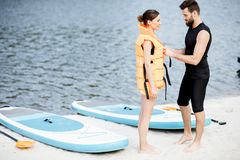 Wearing life vest on the beach. Male instructor helping to wear life vest on the women preparing to surf on the standup paddleboard royalty free stock photography