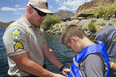 Wearing a Life Vest. County Sheriff's deputy shows a young man the proper way to wear, adjust, and fasten a life vest flotation device Stock Image