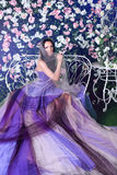 Wearing long purple dress sitting on the bench in a flower garden Stock Images