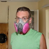 Wearing a Mold Mask. Caucasian man wearing a pink and gray ventilator mask that helps protect his health from mold as he works on a home renovation project stock photography