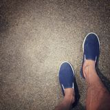 Wearing a pair of blue loafers. On the way stock image