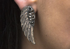 Wearing a silver metal wing earing Stock Images