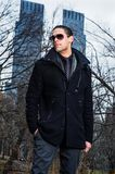 Portrait of Young Man in New York. Wearing sunglasses a young guy is standing outside and looking away. The background is two high business buildings Stock Images