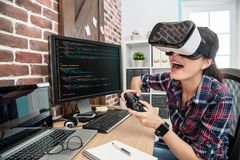 Wearing virtual reality goggles and playing game. Woman wearing virtual reality goggles and playing thru the game controller excitedly stock photography