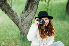 Wearing a white sweater and black hat in blooming garden. Beau Stock Photography