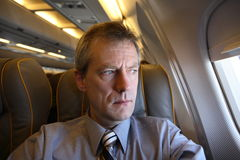 Weary air traveller. A weary business air traveller looks out of his airplane window Stock Images