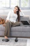 Weary businesswoman sitting on sofa. After work, resting stock images