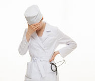 Weary doctor closing her face. White background Stock Photography
