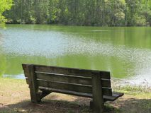 A weary old bench provides a resting place by a serene waterway stock photography
