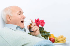 Weary senior gentleman uses his sore throat spray. Sore throat treatment. Senior aged man lies on hospital bed and uses his new sore throat medicine Royalty Free Stock Photo