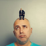 Weary senior man with small businessman. On his head Stock Photography