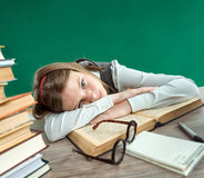 Weary teen girl going to sleep at the desk lying down her head on an open book Royalty Free Stock Photography