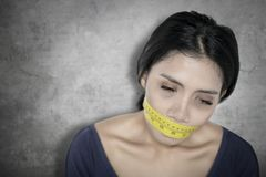 Weary woman covers her mouth with measure tape. Picture of a weary woman covering her mouth with measure tape. Diet concept royalty free stock photography