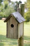 Weasthered Wooden Bird House. A bird house against a country rural setting in the vertical or portrait view Stock Photo