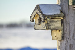 Weather-beaten birdhouse in winter. Weather-beaten birdhouse with snow on roof in winter Stock Photography