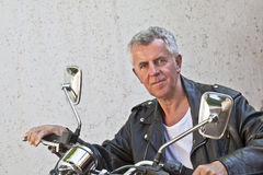 Weather beaten face Rider sat on a Motorcycle Royalty Free Stock Photography