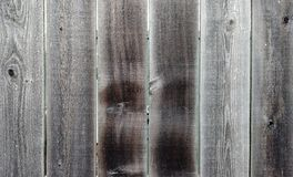 Weather-beaten Wooden Fence for Background or Wallpaper. Old Weather-beaten Wooden Fence With Rough Cut, Cracked Planks. Rough fence with worn, splintered Royalty Free Stock Image