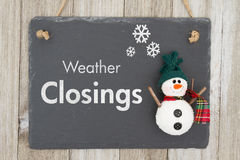 Weather closing sign. A chalkboard sign with a snowman with text Weather Closing on weathered wood Stock Photo