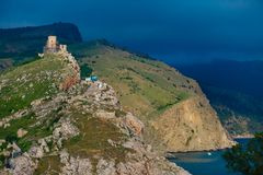 Weather contrast. Genoese fortress ruins on high hill stock photography