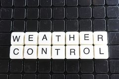 Weather control text word crossword. Alphabet letter blocks game texture background. White alphabetical letters on black Stock Images