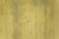 Weather damaged old yellow gray concrete wall with peeling paint. rough surface texture. A weather damaged old yellow gray concrete wall with peeling paint stock photography