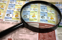 Weather forecast. A magnifying glass on a printed weather forecast in a newspaper Stock Images