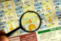 Weather forecast. A magnifying glass on a printed weather forecast in a newspaper royalty free stock image