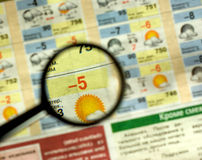 Weather forecast. A magnifying glass on a printed weather forecast in a newspaper Stock Photos