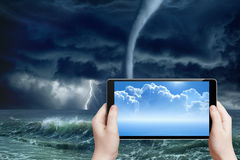 Weather forecast, augmented reality. Concept of augmented reality, weather forecast - abstract tablet pc in hands, sunny weather, stormy weather, tornado on sea stock images