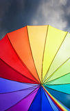 Weather, forecast concept. Rainbow umbrella on stormy sky background Royalty Free Stock Photography