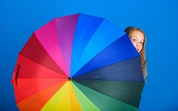 Weather forecast concept. Stay positive though rainy day. Brighten up life. Kid peek out colorful rainbow umbrella. Color your life. Girl cheerful hide behind royalty free stock image