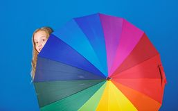 Weather forecast concept. Stay positive though rainy day. Brighten up life. Kid peek out colorful rainbow umbrella royalty free stock image